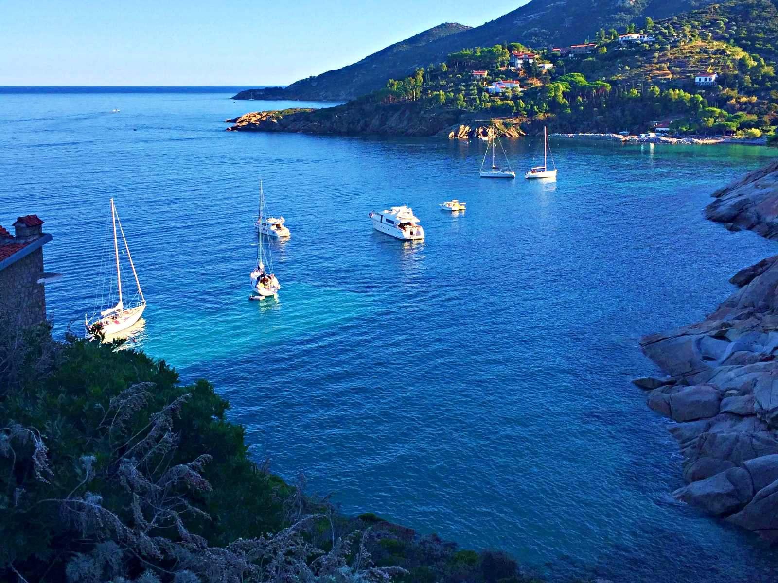 spiaggia delle cannelle isola del giglio vista dall'alto con barche in acqua cristallina